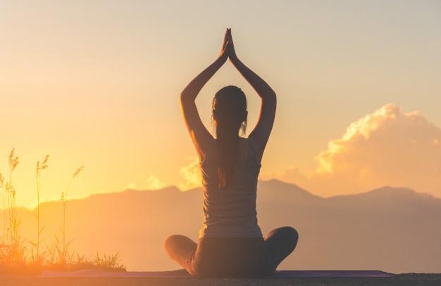 Femme pratiquant le yoga avec un levé de soleil